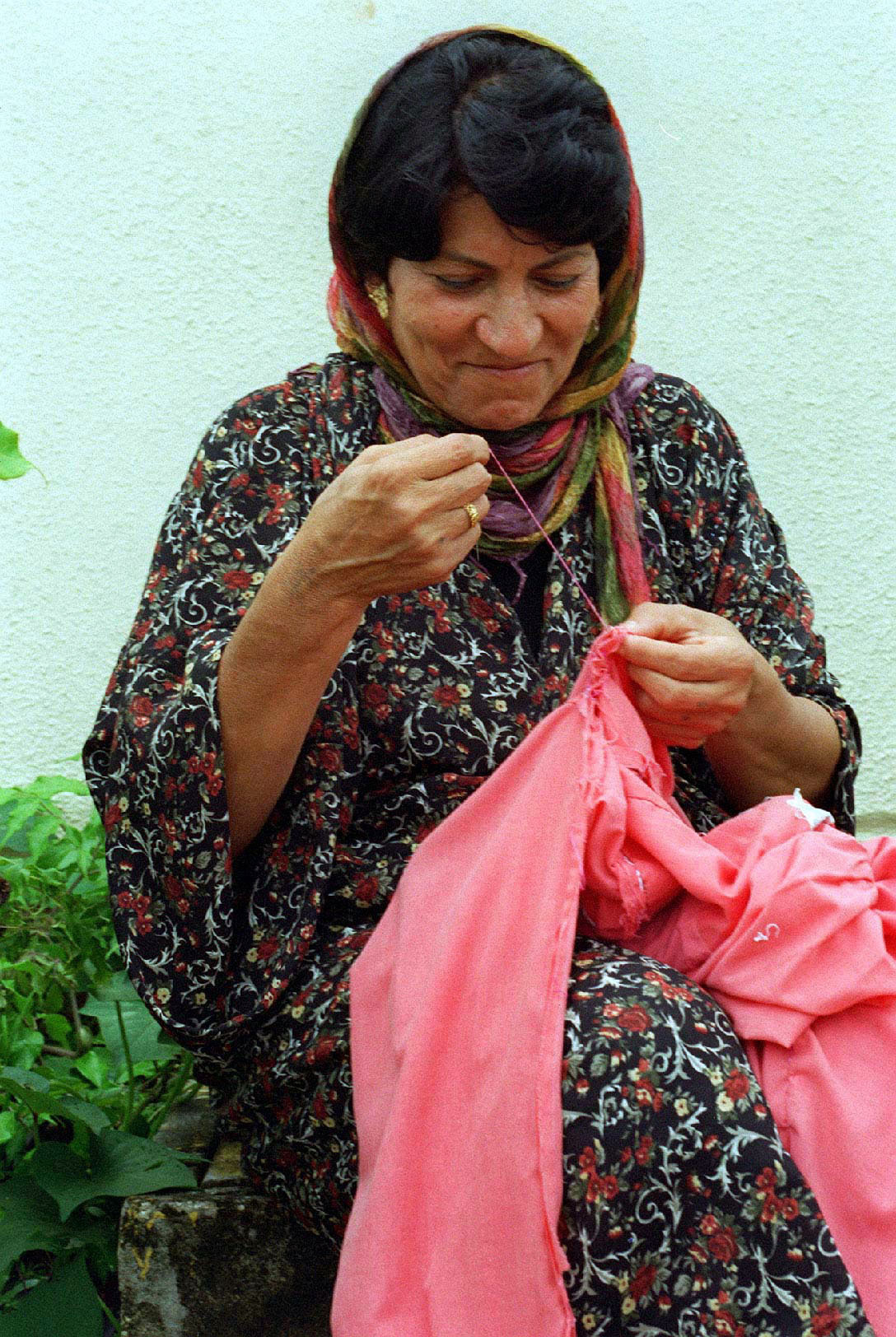 """""""A Kurdish woman passes time sewing while outside her temporary residence at Andersen Air Force Base, Guam, as part of Operation PACIFIC HAVEN…""""The operation, a joint humanitarian effort conducted by the US military, entails the evacuation of over..."""