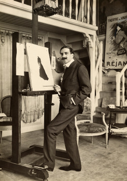 An informal portrait of a well dressed fashion designer at his easel in France, 1918