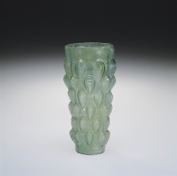 "Object of the Week: Knobbed and Lotus-Bud Beaker, possibly Syria, Roman Empire, 1-99. 64.1.10. The knobbed pattern on this tall vessel was formed when a bubble of hot glass was inflated into a mold. Often described as a ""lotus bud"" because the knobs resemble the bud of the lotus, this pattern was very popular in the first century A.D. Such beakers were made in many sizes; this example is impresssively large at 20.2 cm tall and 8.7 cm wide."