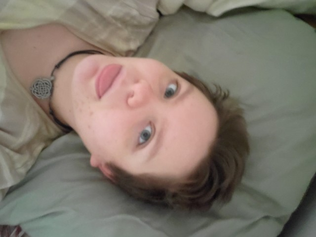 a slightly out of focus selfie of a white passing man sticking his tongue out he is laying on his bed and looking directly into the camera his eyes are blue and he has a young slightly chubby face