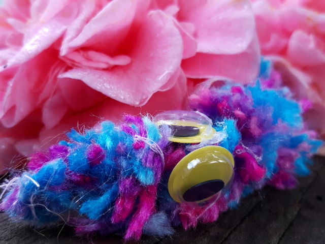 A blue, pink and purple handmade worm on a string named Jim sitting on a redwood tree branch.