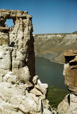 People peer through a natural window in the castellated cliffs above the river in White Cliffs, Montana, 1971
