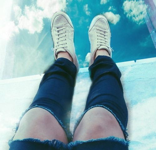 tênis branco sapatos calça jeans rasgado despojada céuazul nuvens fashion photography Photo